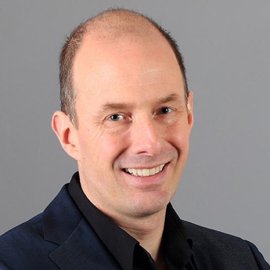 Headshot of a smiling man with a dark blazer