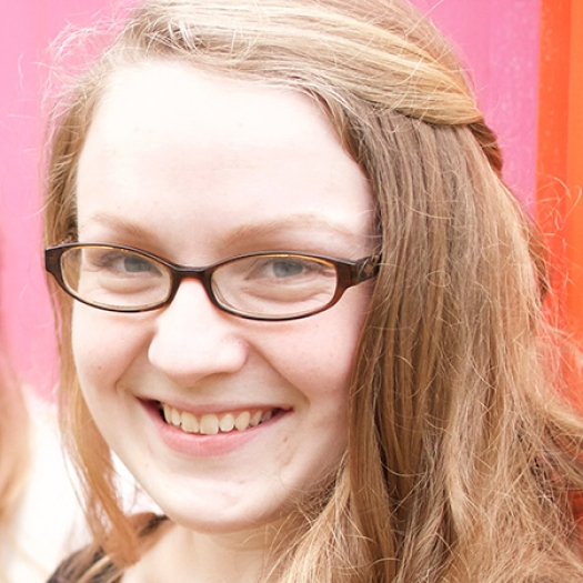 Headshot of a smiling woman wearing glasses