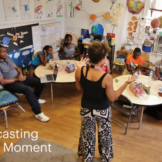 "Elementary school students sit at round tables in a classroom. Behind them are colorful decorations, classroom projects, and school supplies. A woman stands at the front of the room and a man sits to the left. A headline on the image reads, ""Recasting the Moment."""