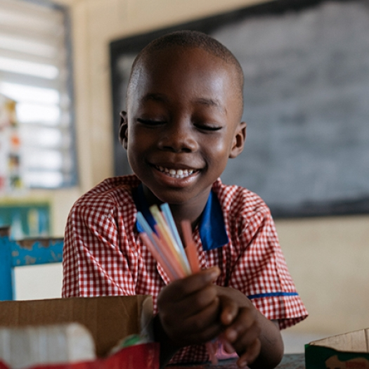 A child in a classroom in Ghana smiles while holding a handful of pens