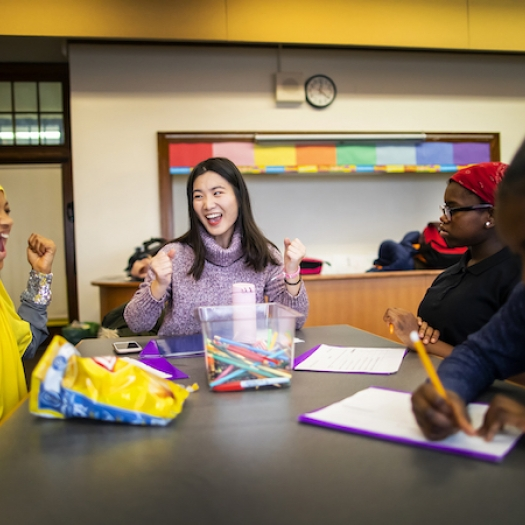 Shiyu Sun, a Penn GSE counseling student, and Philadelphia middle schooler Ciani Patton-Collins laugh together during a mentoring session.