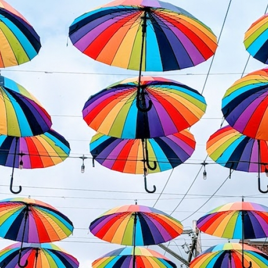 Opened rainbow patterned umbrellas displayed hanging over a street.
