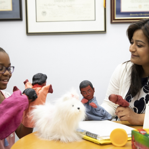 A student and a school counselor use dolls during a counseling session.