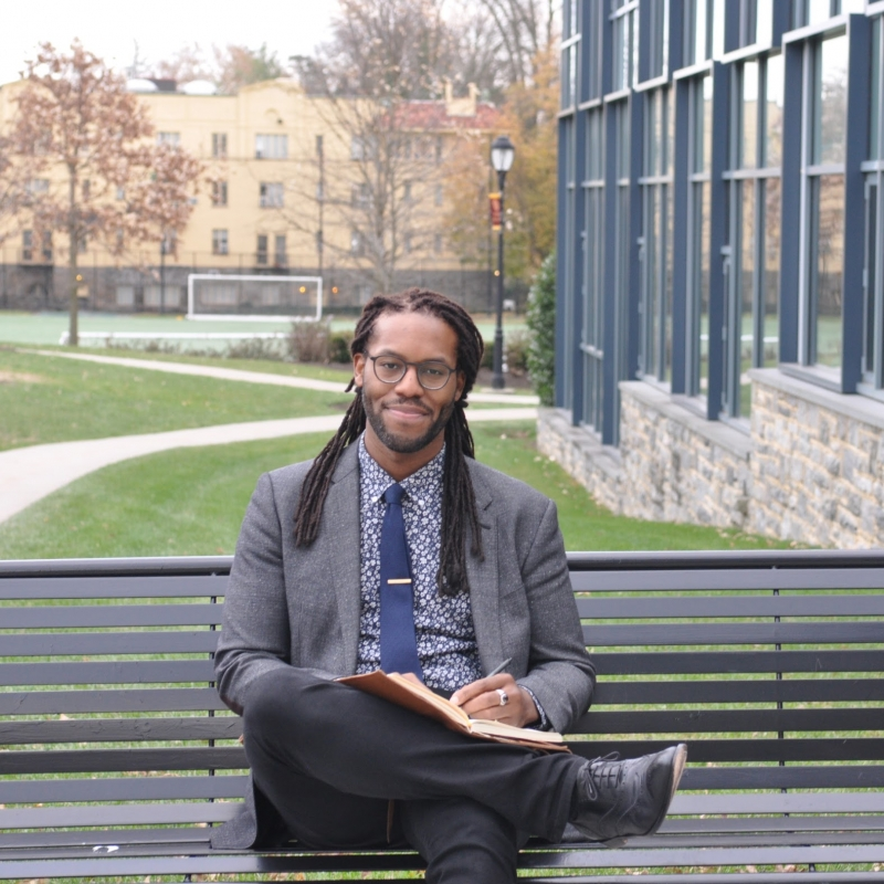 Brendon Jobs sitting on a bench on a campus