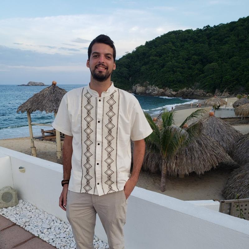Diego Zelaya standing on a balcony above a beach