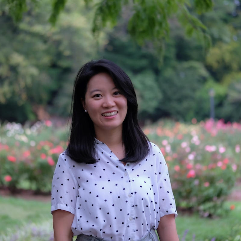 Lys Lin standing in front of a flower garden