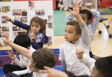 Children raise their hands while sitting on a mat in Kindergarten classroom