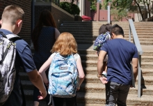 Students with backpacks walking up school steps