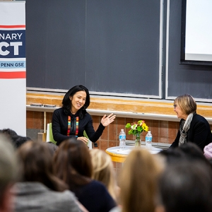 Angela Duckworth and Dean Grossman sit opposite each other conversing before an audience