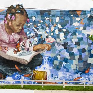 Painting of girl reading book with butterflies flying out.