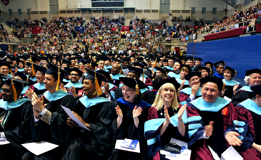 Students in caps and gowns sitting and clapping