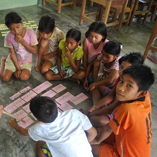 Children sitting on ground looking at index cards