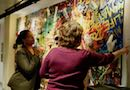 Two women look at the painting Education Not Incarceration.
