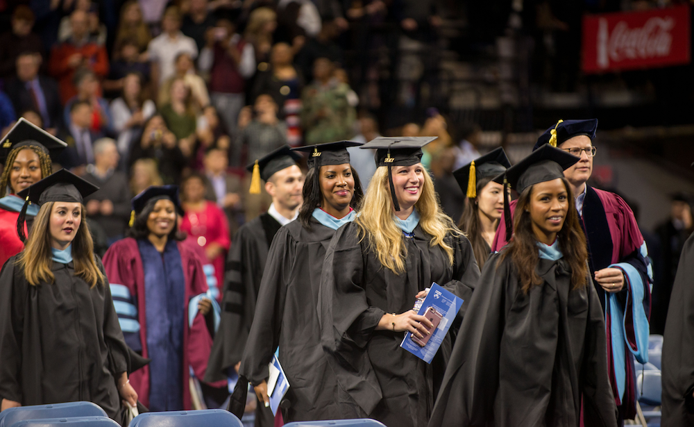 Penn GSE graduates in caps and gowns walking at Commencement