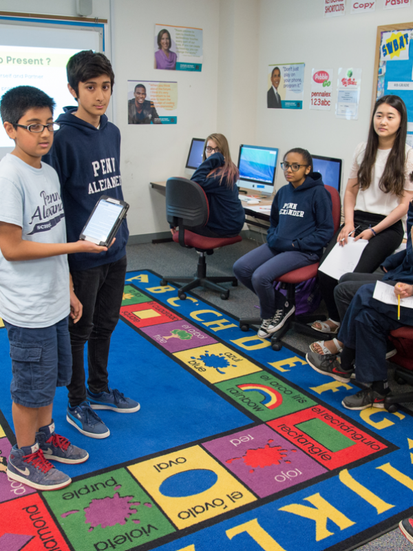 Middle school students with tablet standing at front of class