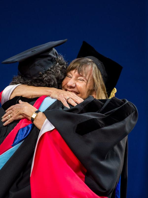 Dean Grossman and a student embrace onstage at graduation.