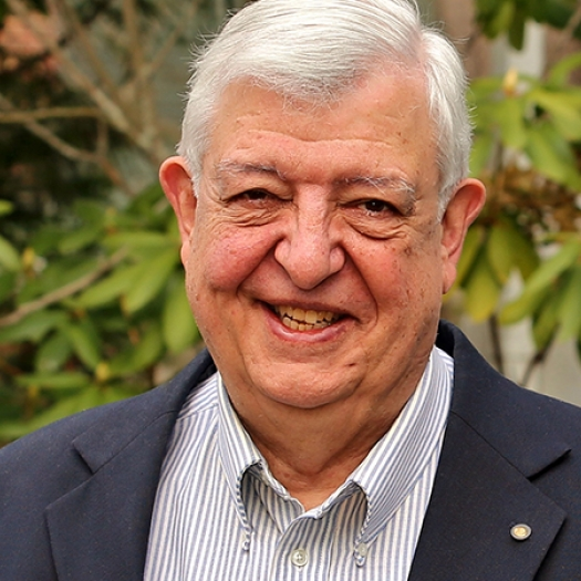 Smiling man with white hair and suit jacket