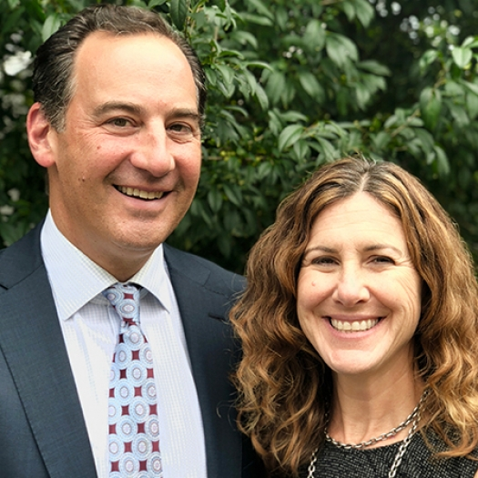 A man in a suit and tie and a woman in a black blouse smiling while standing outdoors