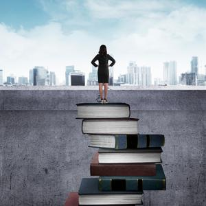 Woman standing on pile of books, looking out at a city skyline.