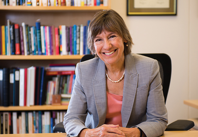 Penn GSE Dean Pam Grossman smiling at desk with bookshelf in background.