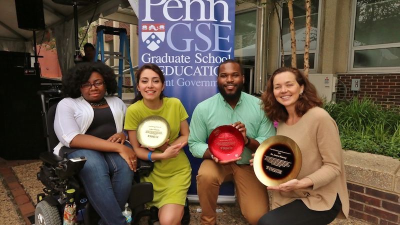 A representative from GSE Student Government poses with 3 student award recipients, who are holding their award plates