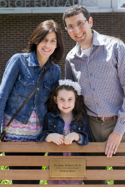 "Photo caption: Josh (right), along with his wife, Michele (left), and daughter, Brittany (center), visit the bench in front of Penn GSE that Josh donated ""in honor of his amazing daughter Brittany Berlin."""