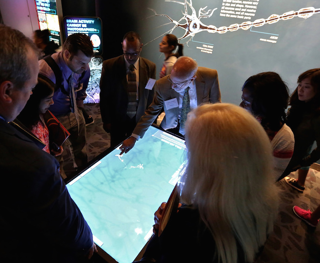 Superintendents around a multimedia exhibit